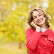 Stock Photo: Young womtalking on cell phone in autumn park