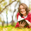 Portrait of a gorgeous brunette woman reading a book in the autumn park — Stock Photo