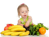 Child eating vegetable and fruit. — Stock Photo