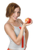 Portrait of happy smiling woman in fitness wear with apple. isolated on white background — Stock Photo
