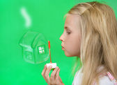 The girl blows a soap bubble - the house of which dreams. on a green background — Stock Photo