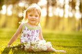 The nice little girl with flowers on the grass in summertime — Stock Photo