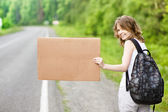 Young girl hitchhiking with cardboard — Stockfoto