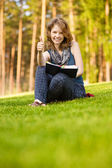 Young beautiful woman on green summer meadow reads textbook. — Stockfoto