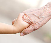 Hands of young child and old senior — Stock Photo