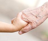 Händerna på barn och gamla senior — Stockfoto