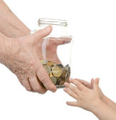 Hands of the elderly person hand over to glass jar with coins in hands of the child. isolated on white background — Stock Photo