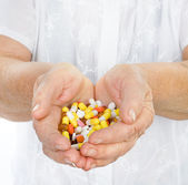 Hand of the old woman with pills. isolated on white background — Stock Photo