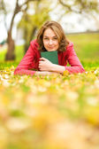 Autumn woman on leafs with the book — Stock Photo