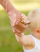 Hands of a grandfather and child — Stock Photo
