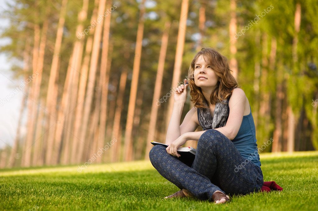 Young woman with book on green grass at park — Stock Photo #13837263