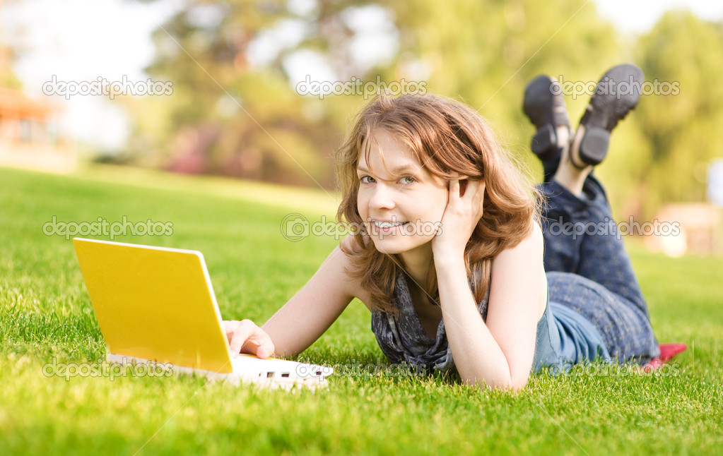 College student lying down on the grass working on laptop at campus — Stock Photo #13837465