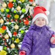 The little girl in the wood near the decorated Christmas tree — Stock Photo