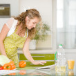 Pregnant woman using a tablet computer to cook in her kitchen — Stock Photo