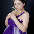 Happy pregnant woman with flowers, looking at camera. on dark background — Stockfoto