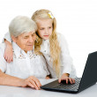 Young girl teaching and showing new computer technology to her grandmother — Stock Photo