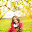 Stock Photo: Young womreading book in autumn park