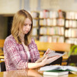Girl with electronic pad in library — Stock Photo #18034359