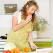 Pregnant woman consulting a recipe while cooking in her kitchen — Stock Photo #18034395