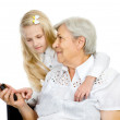 Young smiling granddaughter showing and teaching a mobile phone to her grandmother — Stock Photo