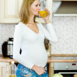 Pregnant woman drink juice in the house kitchen — Stockfoto