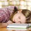 Female student sleeping in a university library — Stock Photo