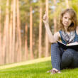 Cute smiling woman holding book in the summer park — Stock Photo