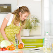 Pregnant woman relaxing with her tablet while cooking some vegetables in the kitchen — Stock Photo #18034647