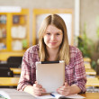 Teenage girl using electronic tablet at library — Stock Photo #18034667