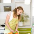 Pregnant woman relaxing with her tablet while cooking some vegetables in the kitchen — Stock Photo