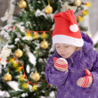 Girl with Santa Claus hat near the decorated christmas tree — Stock Photo