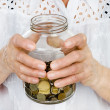 Royalty-Free Stock Photo: Senior woman hands holding jar with coins closeup