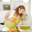 Pregnant woman consulting a recipe while cooking in her kitchen — Stock Photo #18034809