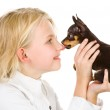 The tiny puppy kisses the girl on a nose — Stock Photo #18034813