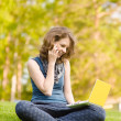 Beautiful girl sitting on the grass working on laptop — Stock Photo