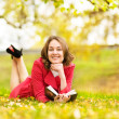 Womlying on grass with book — Stock Photo #18034925