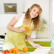 Pregnant mother preparing food in kitchen. Beautiful young caucasian woman reading cooking recipe while making salad. Looking at camera — Stock Photo #18034945