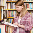 Stock Photo: Pensive student at library surrounded by books