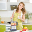 Stock Photo: Portrait of smiling pregnant womcooking in her kitchen. looking at camera.