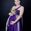 Pregnant woman smiling holding flowers. looking at camera — Stock Photo #18035133
