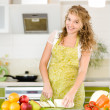 Portrait of a smiling pregnant woman cooking in her kitchen — Stock Photo #18035215