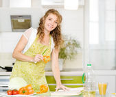 Pregnant mother making healthy food standing happy smiling in kitchen. looking at camera. — Stock Photo