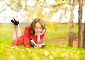 Young nice attentive woman lies on green grass and reads book against city park — Stock Photo