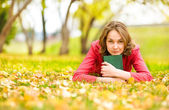 Young beautiful woman lays on a grass with the book — Stock Photo