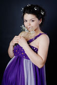 Happy pregnant woman with flowers, looking at camera. on dark background — Stock Photo