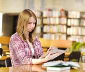 Girl with electronic pad in library — Stockfoto