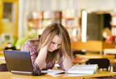 Sad student with laptop working in library — Stock Photo