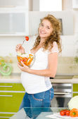 Pregnant woman in kitchen eating a salad smiling — Stock Photo