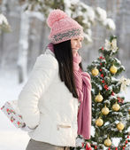 Girl with gift near decorated tree — Stock Photo