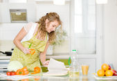Pregnant mother reading cookbook in the kitchen, looking for recipe. woman holding knife, preparing food and making salad — Stock Photo